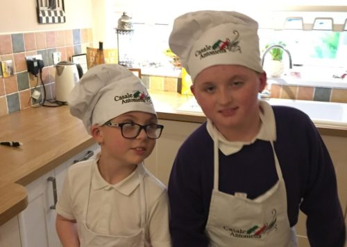 James in chef's hat and apron with a friend in the kitchen