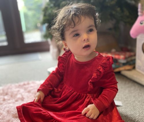 Mya in a red dress sitting on the floor