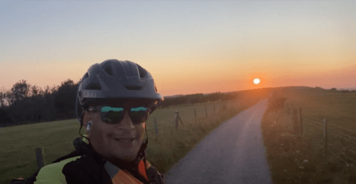 raj with cycle helmet and sunglasses rifing towards the sunset